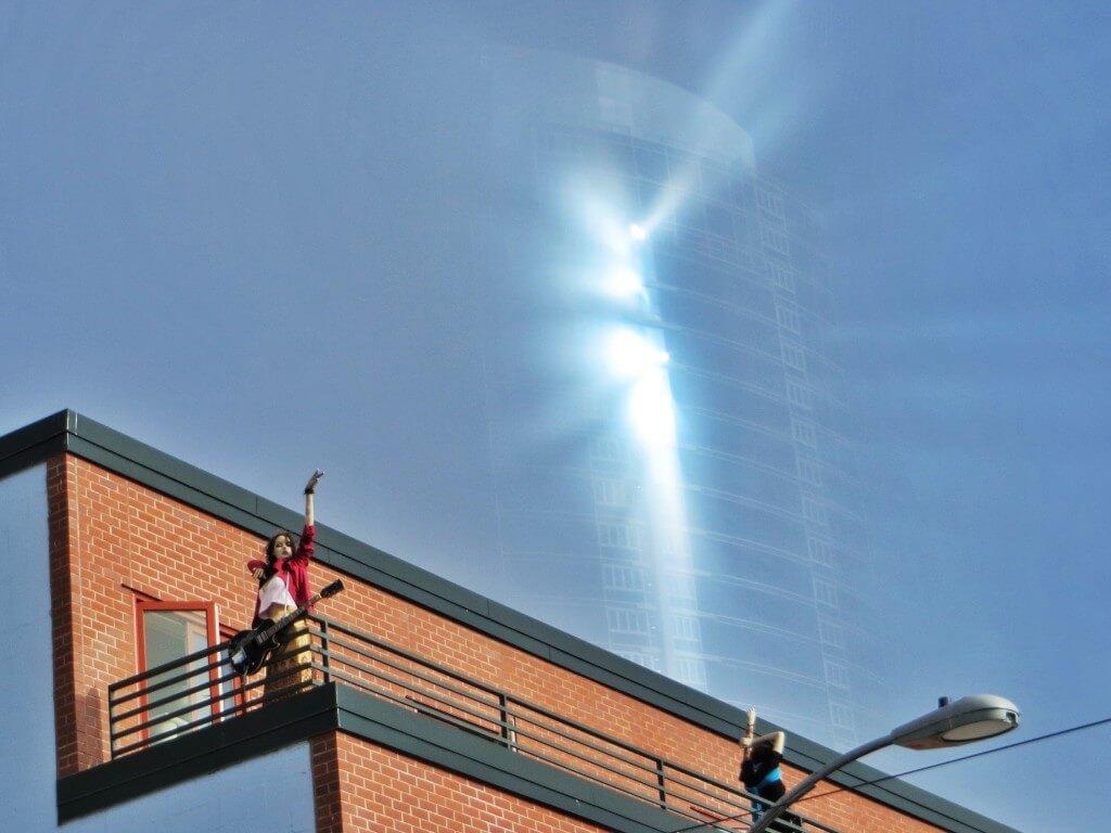 Häkellyttävä valoilmiö: aurinko paistaa jostain raosta sumun keskellä olevan pilvenpiirtäjän ikkunoihin.