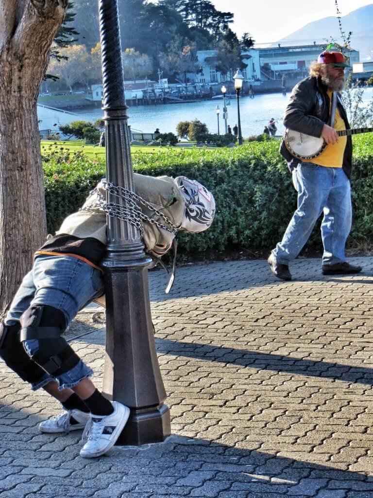 Escapeman ja propellihattuinen banjonsoittaja viihdyttävät raitiovaunuun jonottava turisteja